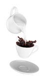 Milk being poured into small cup of coffee.  white background Royalty Free Stock Photos