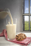 Milk being pouring into glass, chocolate cookie on the side Royalty Free Stock Photos