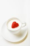 Milk with berry. Strawberry heart inside cup of milk on porcelain saucer Royalty Free Stock Photography