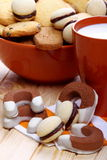 Milk and biscuits at breakfast. Cup of milk with a bowl full of pastries on pine wood Stock Image