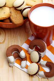 Milk and biscuits at breakfast. Cup of milk with a bowl full of pastries on pine wood Royalty Free Stock Photos