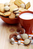 Milk and biscuits at breakfast. Cup of milk with a bowl full of pastries on pine wood Stock Images