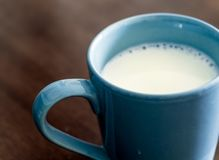 Milk in blue cup on the wooden and top glass table Royalty Free Stock Image