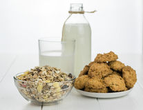 Milk bottle, bowl with muesli and fresh baked cookies on a white wooden table. Stock Photos