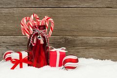 Milk bottle with candy canes, baubles and gifts, in snow Royalty Free Stock Photos