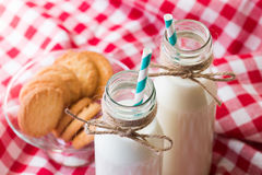 Milk bottle and cookies in a glass bowl stock photo