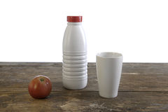 Milk bottle, cup and apple on old weathered table Stock Image