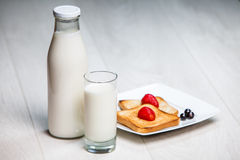 Milk bottle and glass with toasts Stock Images