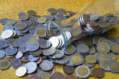 Milk bottle lying beside pile of Coins. From various countries on golden glittering background Royalty Free Stock Image