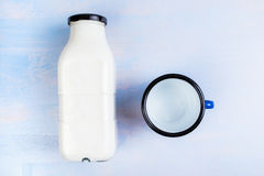 Milk bottle and metal cup, top view Royalty Free Stock Photos