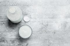 The milk in the bottle. On a rustic background stock image