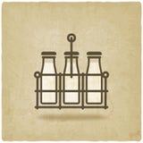 Milk bottles in basket on old background Royalty Free Stock Images