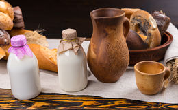 Milk bottles in front of bread loaves Royalty Free Stock Photography