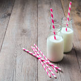 Milk bottles with retro striped straws Royalty Free Stock Images