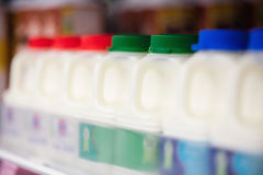 Milk bottles tidied in shelf Royalty Free Stock Images
