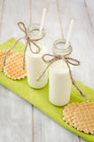 Milk bottles with waffles on a green napkin. Two bottles of milk with waffles on a green table napkin.  Retro bottles of milk standing on old kitchen table Stock Image