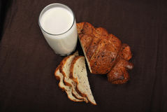 Milk and bread. On a dark brown background Stock Photos