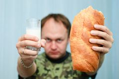 Milk And Bread. Portrait of a man in camouflage offering glass of milk and a loaf of bread Stock Photo