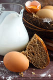 Milk, bread and eggs. Milk, bread and egg in the nest. Baking ingredients, wooden background Royalty Free Stock Photo