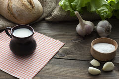 Milk, bread , garlic and lettuce Stock Images