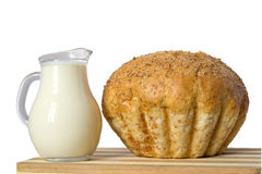 Milk and bread. Milk in a milkman and a loaf of bread are on the cutting board Stock Photos
