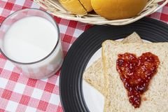 Milk with breads and strawberry jam. Top view of strawberry jam shaped a heart symbol on the bread with milk on the table Stock Photography
