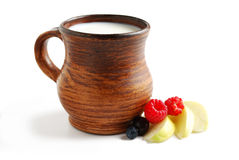 Milk in brown ceramic bowl and summer fruits. Isolated on a white background Royalty Free Stock Images