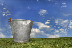 Milk bucket. In the grass against a blue sky Royalty Free Stock Image