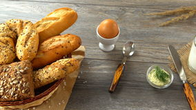 Milk, butter, cookies, egg, and fresh bread on a rustic wooden table. Countryside breakfast. stock video