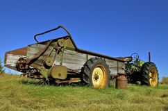 Milk can left by old manure spreader Stock Photography