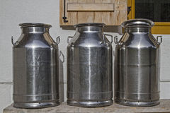 Milk cans in front of the mountain hut Royalty Free Stock Photo