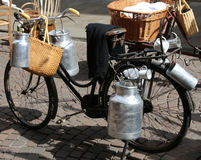 Milk cans transported on old bike of the milkman. Aluminium milk cans transported on old bike of the milkman Royalty Free Stock Photography