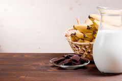 Milk in the carafe on the background of bananas and chocolate Royalty Free Stock Images