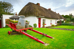 Milk cart at the cottage houses in Adare, Ireland. Irish traditional cottage houses in Adare village Stock Images