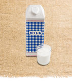 Milk carton and glass with milk on a sackcloth Stock Image