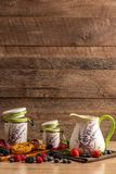 Milk in ceramic jug and two size jars with biscuits and mix of wild berries on wooden background royalty free stock photos