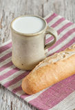 Milk in ceramic mug and baguette on the wooden board Stock Photos