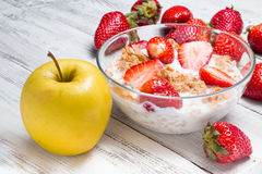 Milk, cereal, apple and strawberries on a wooden table. Royalty Free Stock Photos