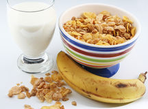 Milk, cereal and fruit. A closeup of a glass of milk, a bowl of cereal and a banana royalty free stock photo