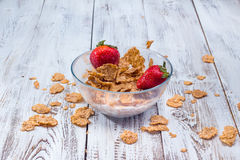 Milk, cereal and strawberries on a wooden table. Stock Images