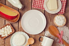 Milk and cheese around empty plate on wooden background. View from above. Royalty Free Stock Photo