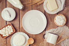 Milk, cheese and butter around empty white plate on wooden background. Healthy eating concept. View from above. Stock Image