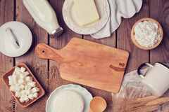 Milk, cheese and butter with cutting board on wooden background. View from above. Stock Photography