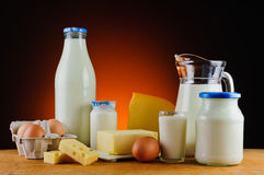 Milk, cheese, butter, eggs and cream. Still life with milk, cheese, butter, eggs and cream on a wooden table Stock Photography