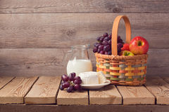 Milk, cheese and fruit basket on wooden table. Jewish holiday Shavuot celebration Royalty Free Stock Photos