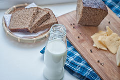 Milk, cheese and rye bread. Bottle of milk, cheese and rye brown bread on rustic gingham table cloth Royalty Free Stock Photo