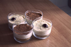 Milk cheesecake in glasses, decorated with coffee crumbs, cookies and cherries, on a wooden table on a blurred background in the e Stock Images