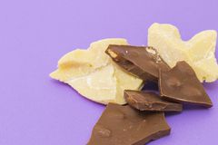 Milk chocolate with almond and cocoa butter. On violet background Royalty Free Stock Photo