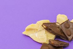 Milk chocolate with almond and cocoa butter. On violet background Royalty Free Stock Photography