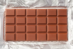 Milk Chocolate Bar. In opened foil wrapping Royalty Free Stock Photos